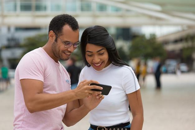 Frohe freunde, die auf straße stehen und smartphone verwenden