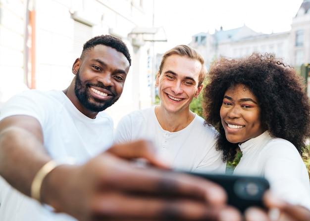 Frohe freunde im freien, die selfie nehmen