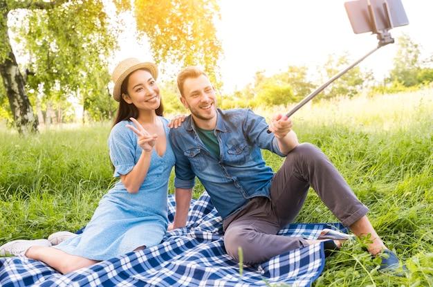 Frohe gemischtrassige erwachsene paare, die selfie nehmen