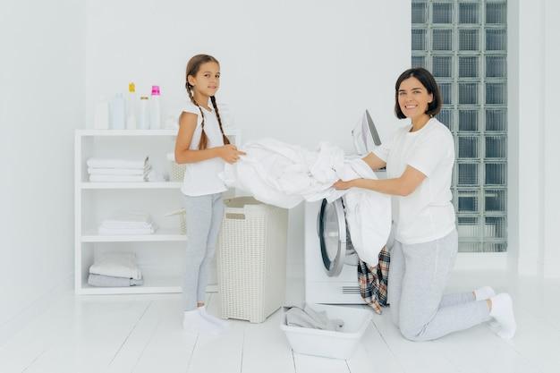 Frohe hausfrau wäscht sich mit einem kleinen entzückenden helfer. mutter und tochter waschen ihre wäsche in der waschküche und legen wäsche in die waschmaschine. frau steht auf den knien in der nähe von waschmaschine. hausarbeit-konzept