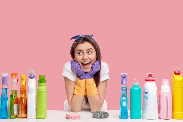 Frohe hausmeisterin hält die hände unter dem kinn, schaut glücklich weg, trägt stirnband und lässiges t-shirt, verwendet reinigungsmittel und schwämme zur reinigung, isoliert über der rosa wand. haushaltskonzept.
