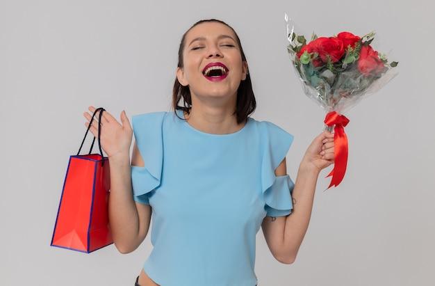 Frohe hübsche junge frau mit blumenstrauß und geschenktüte