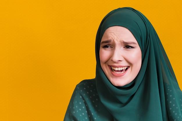 Frohe islamische frau, die weg gegen gelben hintergrund schaut