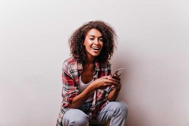 Frohe junge dame im lässigen outfit, das auf weiß mit telefon sitzt. schönes afrikanisches mädchen, das smartphone während des schusses benutzt.