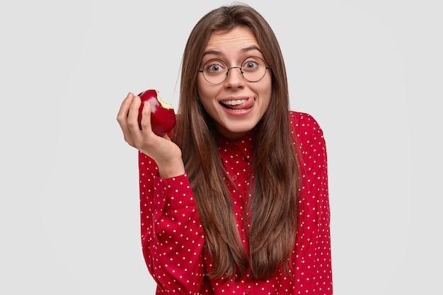 Frohe junge dame isst leckeren apfel, leckt sich gerne die lippen, hat einen fröhlichen gesichtsausdruck