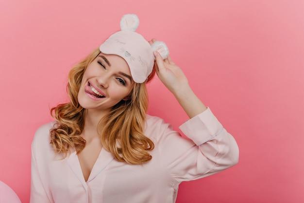 Frohe junge dame mit glänzendem blondem haar, das mit hübschem lächeln aufwirft. innenfoto des freudigen positiven mädchens in der schlafmaske lokalisiert auf rosa wand.