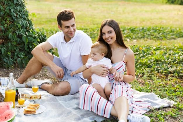 Frohe junge familie mit kleinem baby, die zeit zusammen verbringt