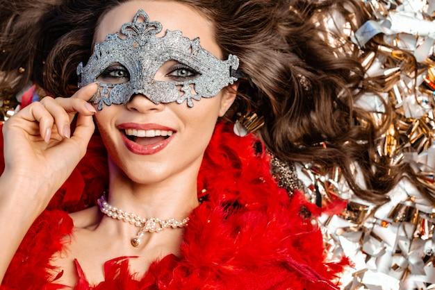 Frohe junge frau, die auf dem boden unter der goldenen lamettanahaufnahme liegt, die eine karnevalsmaske trägt