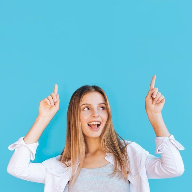 Frohe junge frau, die aufwärts ihren finger gegen blauen hintergrund zeigt