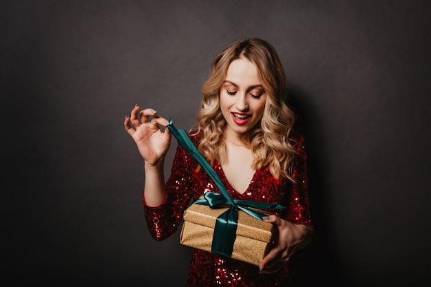 Frohe junge frau, die ihr geburtstagsgeschenk öffnet