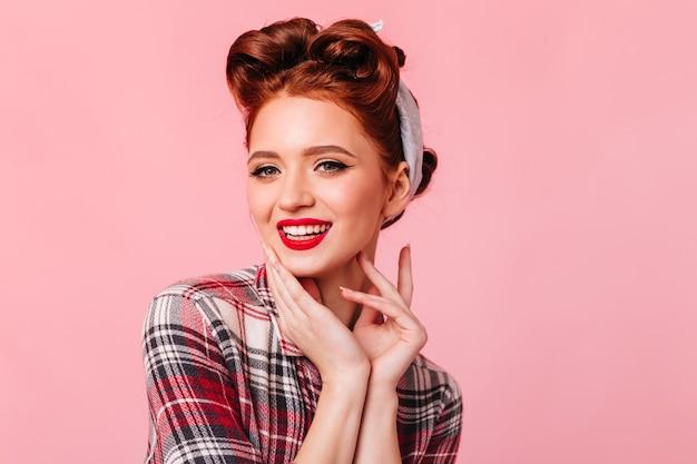 Frohe junge frau im weinlese-outfit, das an der kamera lächelt. studioaufnahme der wunderschönen pinup lady mit roten lippen.