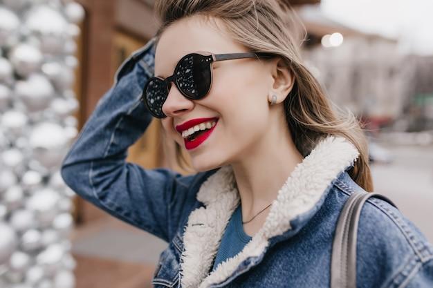 Frohe junge frau in jeanskleidung, die ihre haare berührt, während sie durch die stadt geht. außenaufnahme des schönen mädchens in der guten stimmung, die im frühlingstag entspannt.