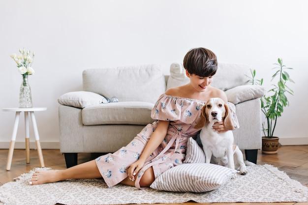 Frohe junge frau mit glänzendem braunem haar, das mit ihrem niedlichen beagle-welpen auf dem boden aufwirft. innenporträt des aufgeregten mädchens im kleid mit blumendruck, der auf dem teppich mit hund sitzt