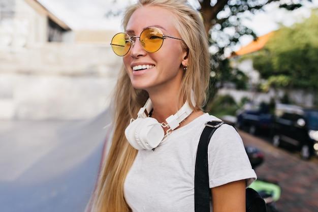 Frohe junge frau mit glücklichem gesichtsausdruck, der in kopfhörern durch stadt geht. hübsche blonde frau in der gelben sonnenbrille lachend, während sie auf unscharfem straßenhintergrund aufwirft.