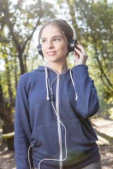 Frohe junge frau mit kapuze sweatshirt und kopfhörer