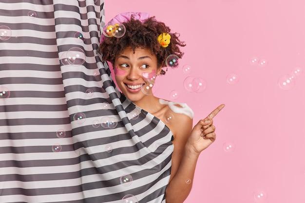 Frohe junge frau mit lockigem haar duscht regelmäßig regelmäßig schönheitsroutinen zeigt auf leere rosa wand versteckt nackten körper hinter vorhang empfiehlt hygieneprodukt