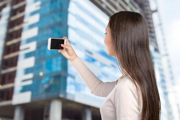 Frohe junge frauen, die selfie durch ihr intelligentes telefon machen