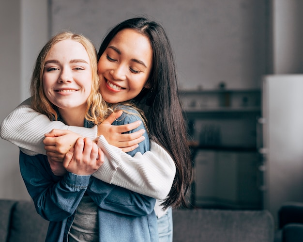 Frohe junge freundinnen, die zu hause streicheln