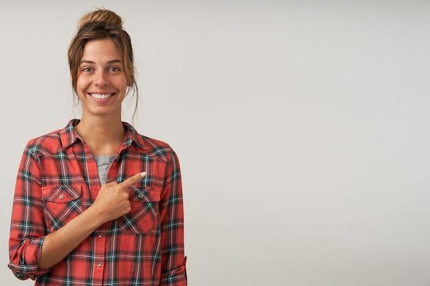 Frohe junge hübsche brünette frau mit brötchenfrisur, die fröhlich lächelt, während sie mit erhöhtem zeigefinger beiseite zeigt, lokalisiert über weißem hintergrund in freizeitkleidung