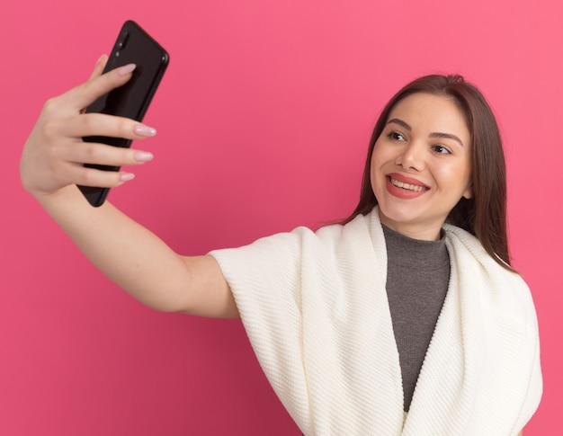 Frohe junge hübsche frau, die selfie macht