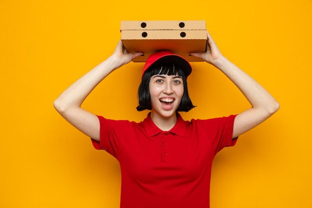Frohe junge kaukasische lieferfrau, die pizzakartons über ihrem kopf hält