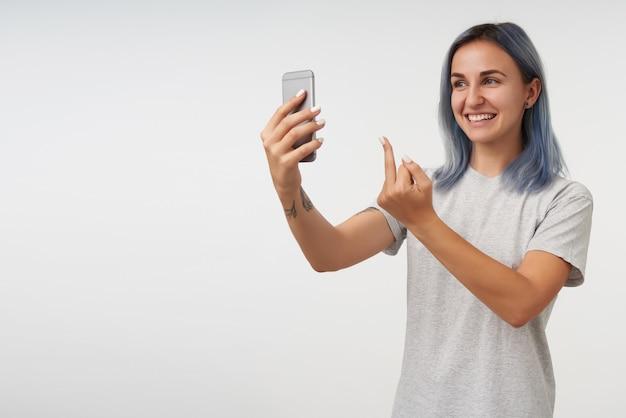 Frohe junge schöne tätowierte frau mit kurzen blauen haaren, die fickgeste zeigt, während sie fröhlich lächelt und graues einfaches t-shirt trägt, während sie auf weiß posiert