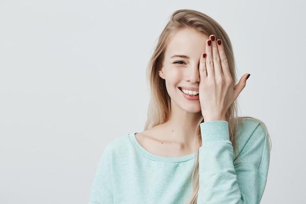Frohe kaukasische frau mit langen gefärbten haaren, hellblauem pullover tragend, ihr auge mit der hand schließend. glückliche positive frau, die gute und verspielte stimmung hat.