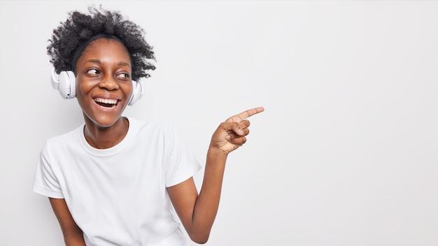 Frohe lächelnde dunkelhäutige frau mit lockigem haar zeigt weg auf leerzeichen