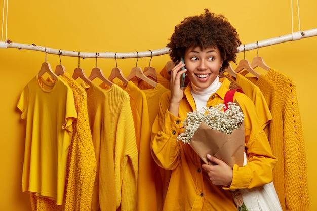 Frohe lockige frau mit fröhlichem gesichtsausdruck, ruft freund an, hält schönen blumenstrauß, trägt tasche, posiert gegen gelbe helle kleidung auf lumpen