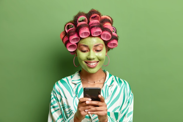 Frohe mischlingsfrau trägt lockenwickler trägt nährende tonmaske für die hautbehandlung trägt seidenanzug hält handy surft soziale netzwerke isoliert über grüner wand