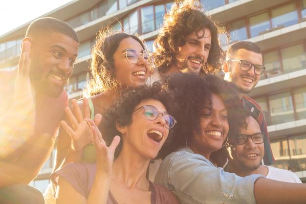 Frohe multiethnische freunde, die lustiges gruppen-selfie nehmen