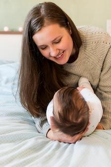 Frohe mutter, die baby in den armen hält