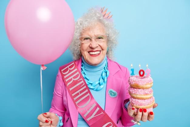 Frohe optimistische frau feiert 102. geburtstag hält haufen donuts und aufgeblasenen heliumballon in festlicher kleidung gekleidet sieht wunderschön aus, gepflegt, trägt helles make-up