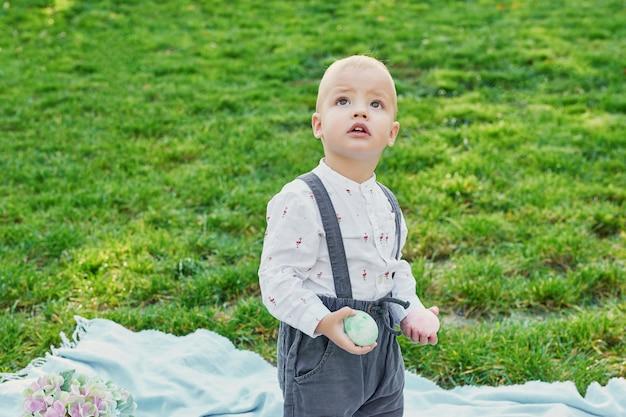 Frohe osterhase. kind, das spaß im freien hat. kind, das mit eiern und kaninchen auf grünem gras spielt.