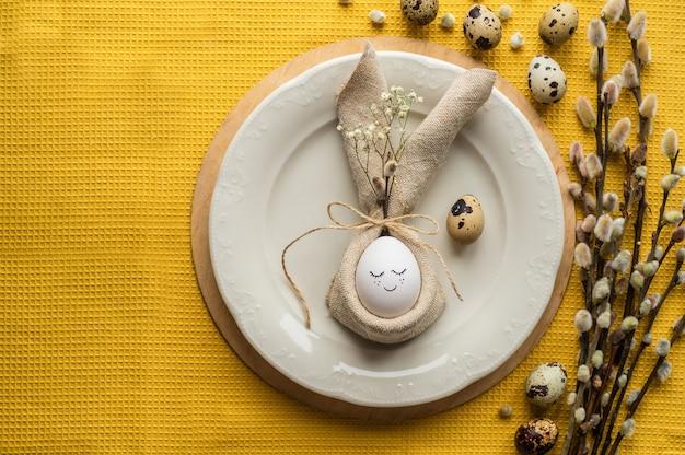 Frohe osterkarte. nettes ei in einer serviette in form eines häschens auf einer keramikplatte.