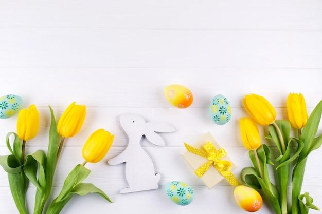 Frohe osterkarte. rahmen mit gelben tulpen und ostereiern und hase mit kopienraum für text auf weißem hintergrund. draufsicht