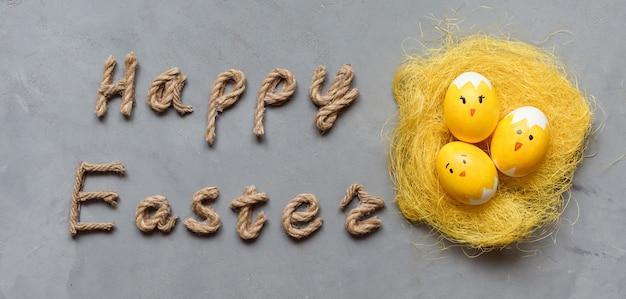 Frohe ostern banner mit leuchtend gelben eiern gemalt als küken mit lustigen gesichtern und seilbeschriftung auf dem grauen hintergrund.