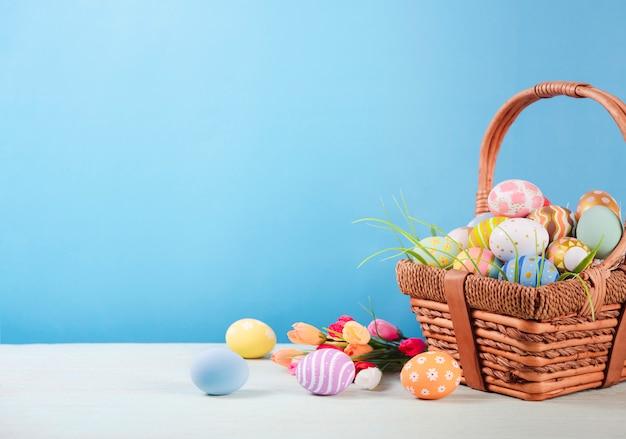 Frohe ostern, bemalte ostern eier im korb auf rustikalem holztisch für ihre dekoration im urlaub. speicherplatz kopieren.