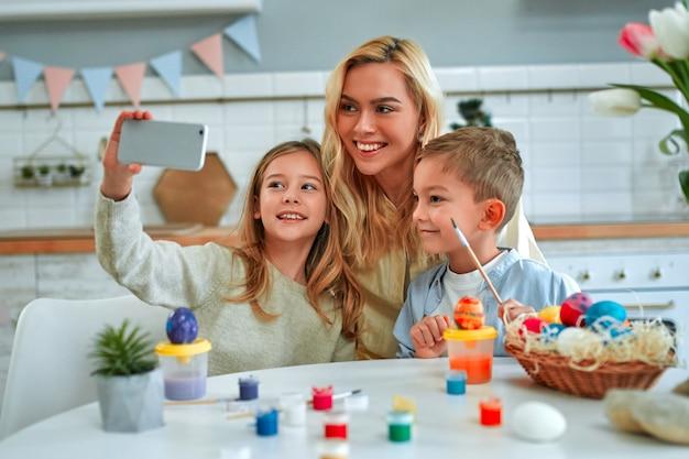 Frohe ostern! charmante mutter mit ihren kindern niedlichen jungen und mädchen machen ein selfie, während sie eier malen. glückliche familie, die sich auf ostern vorbereitet.