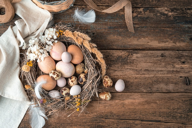 Frohe ostern, festlicher hintergrund mit eiern in einem nest auf einem hölzernen hintergrund.