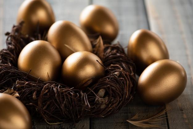 Frohe ostern! golden von ostereiern im nest und von der feder auf hölzernem hintergrund