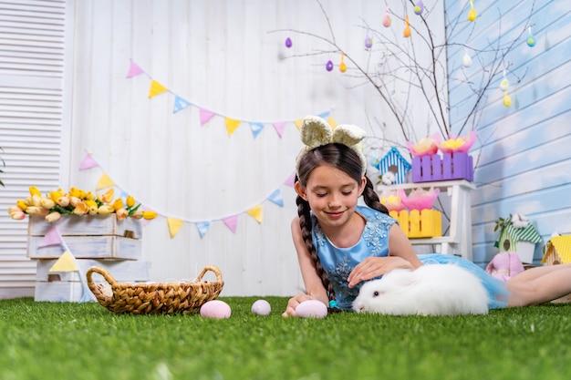 Frohe ostern! hübsches mädchen, das auf gras mit ostereiern und streichelndem kaninchen liegt.