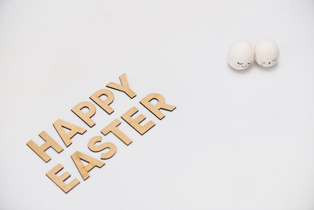 Frohe ostern in holzbuchstaben mit weiß verzierten eiern