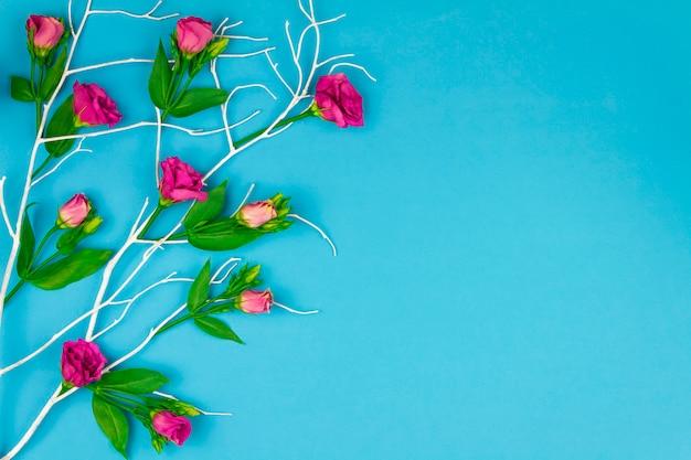 Frohe ostern-konzept. blauer niederlassungsbaum mit den blumen des bunten frühlinges und den bunten ostereiern auf blauem hintergrund