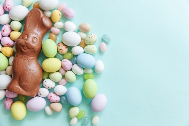 Frohe ostern konzept. osterbonbon schokoladeneier hase und jellybean süßigkeiten lokalisiert auf trendigem pastellblau hintergrund