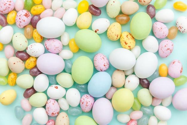 Frohe ostern konzept. schokoladeneier der ostersüßigkeit und geleebonbons lokalisiert auf trendigem pastellblauem hintergrund