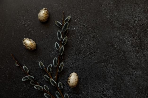 Frohe ostern konzept. vorbereitung auf den urlaub. golden dekorierte ostereierweide auf trendigem grunge zerkratztem dunkelschwarzem schieferhintergrund