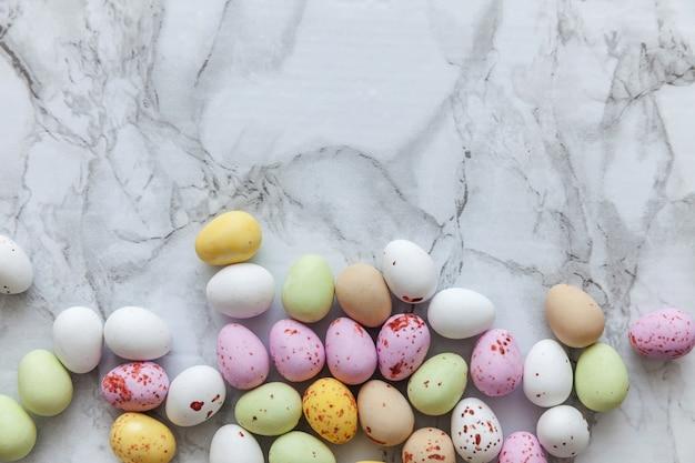 Frohe ostern konzept. vorbereitung auf den urlaub. ostern pastellbonbon schokoladeneier süßigkeiten auf trendigem grauem marmorhintergrund
