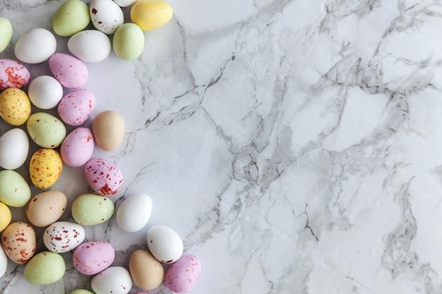 Frohe ostern-konzept. vorbereitung für den urlaub. ostern-pastellbonbonschokolade ärgert bonbons auf modischem grauem marmorhintergrund. draufsicht-kopienraum der einfachen minimalismusebene lage.