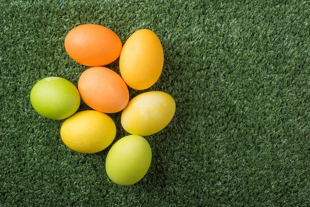 Frohe ostern mit bunten eiern auf der grasoberansicht mit kopienraum